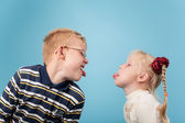 Teenage boy and girl stick out tongues to each other — Stock Photo