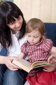 Mother reading a book with her little daughter — Stock Photo
