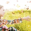 Girl sitting in a meadow in a swarm of flitting butterflies. — Stock Photo #74536759