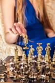 Female hand with elegant gold manicure holding chess piece — Stock Photo