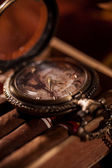 Pocket watch close-up lying on top of the package of Cuban cigar — 图库照片