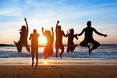 Six people jumping on beach at sunset. — Stock Photo