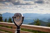 Public view binoculars, operated with coins, on a deck, with the Adirondack mountians in the background — Stock Photo