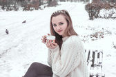 Girl drinking hot tea in the winter landscape, close up — Stock Photo