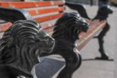 Park bench with cast iron legs in the form of a lion's head — Stock Photo