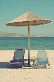 Greece. Kos island. Two chairs and umbrella on the beach. In ins — Stock Photo