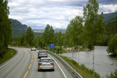 Auto going on a road winding between mountains — Foto Stock