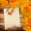 Old grunge paper with autumn maple branch leaves on the wooden b — Stock Photo #51908071