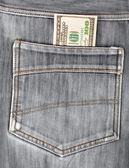 A hundred dollar bills sticking in the back pocket of denim blac — Stock Photo