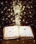 Open book with magic light and magic letters and drawings — Stock Photo