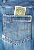 One dollar bill sticking in the back pocket of denim blue jeans — Stock Photo