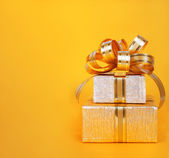 Beautiful  Gift box in gold wrapping paper on abstract backgroun — Stock Photo