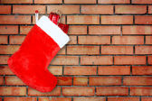 Red christmas boot with gifts on background brick wall — Foto Stock