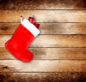 Red christmas boot with gifts on background wooden wall — Stock Photo