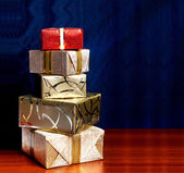 Gift box in gold wrapping paper with ribbon on wooden table  — Stock Photo