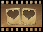 Old paper slides in the form of hearts on abstract grunge backgr — Stock Photo