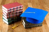 Graduation mortarboard on top of stack of books on wooden backgr — Stock Photo