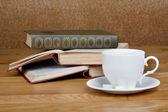 Warme kop van verse koffie op de houten tafel en een stapel boeken — Stockfoto