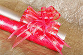 Rolls of multicolored wrapping paper with red bow for gifts on g — Stock Photo