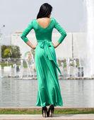 Beautiful young woman in green long dress — Stock Photo