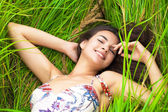 Young woman resting and day lying down on green grass — Stock Photo