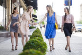 Four beautiful fashion women walking on the street  — Stock Photo