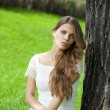 Young pretty girl sitting on green grass — Stock Photo #52894567