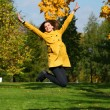 Happy woman in yellow coat jumping in autumn park — Stock Photo #53672575