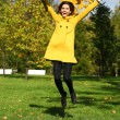 Happy woman in yellow coat jumping in autumn park — Stock Photo #53672581