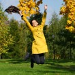 Happy woman in yellow coat jumping in autumn park — Stock Photo #53672603