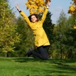Happy woman in yellow coat jumping in autumn park — Stock Photo #53672629