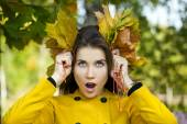Happy young woman in yellow coat in autumn park — Stock Photo