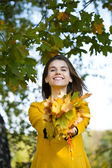 Happy young woman in yellow coat in autumn park — Stockfoto