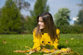 Happy young woman in yellow coat in autumn street — Stockfoto