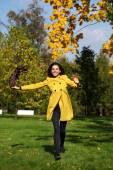 Happy woman in yellow coat walking autumn street — Stock Photo