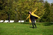 Happy woman in yellow coat walking autumn street — Φωτογραφία Αρχείου