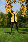 Happy woman in yellow coat jumping in autumn park — Stockfoto