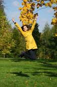 Happy woman in yellow coat jumping in autumn park — Stock Photo