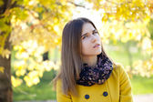 Happy young woman in yellow coat in autumn street — Stock Photo