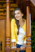Happy young woman standing on the porch of a wooden house — Stockfoto