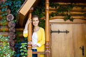 Happy young woman standing on the porch of a wooden house — Stock Photo