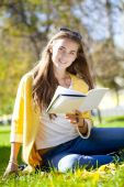 Beautiful schoolgirl sitting in autumn park and reading a book — Stock Photo