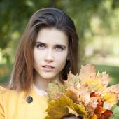 Happy young woman in yellow coat in autumn park — Foto de Stock