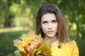 Happy young woman in yellow coat in autumn park — Foto Stock