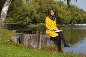 Beautiful young woman in yellow coat — Stock Photo