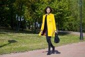 Joven feliz en capa amarilla en otoño calle — Foto de Stock