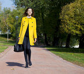 Happy young woman in yellow coat in autumn street — Photo