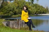 Beautiful young woman in yellow coat — Foto de Stock