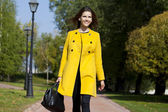 Happy young woman in yellow coat in autumn street — Foto Stock
