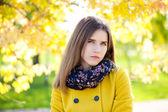 Happy young woman in yellow coat in autumn street — Foto de Stock
